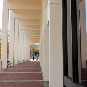 Student walking in front of Powell Building Plaza level